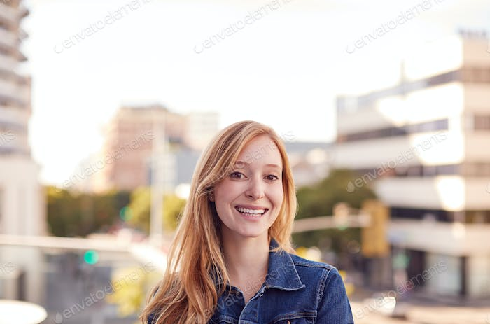 Portrait Of Smiling Young Businesswoman Standing Outside Office Building With City Skyline Behind