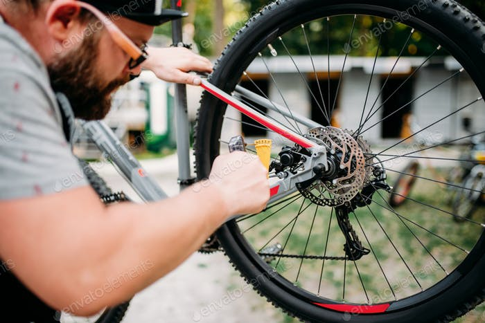 Bicycle mechanic adjusts back disk brakes