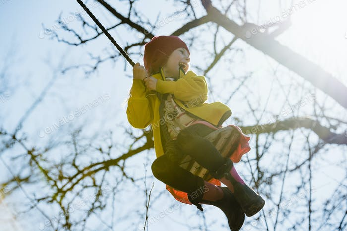 Girl (4-5) swinging on rope