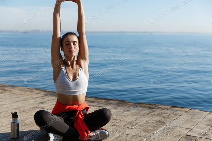 Outdoor shot of relaxed young woman meditating near the sea, practice yoga, sitting in asana on a