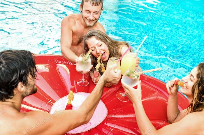 Seitenansicht glücklicher Freunde, die bei einer Poolparty Fruchtcocktails trinken