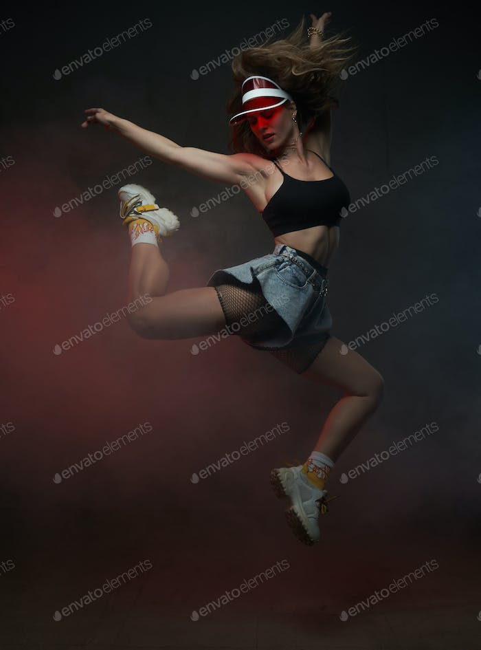 Female dancer with red cap jumping in dark smoke background