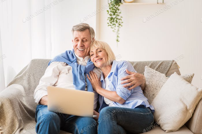Mature man and his wife working with laptop at home