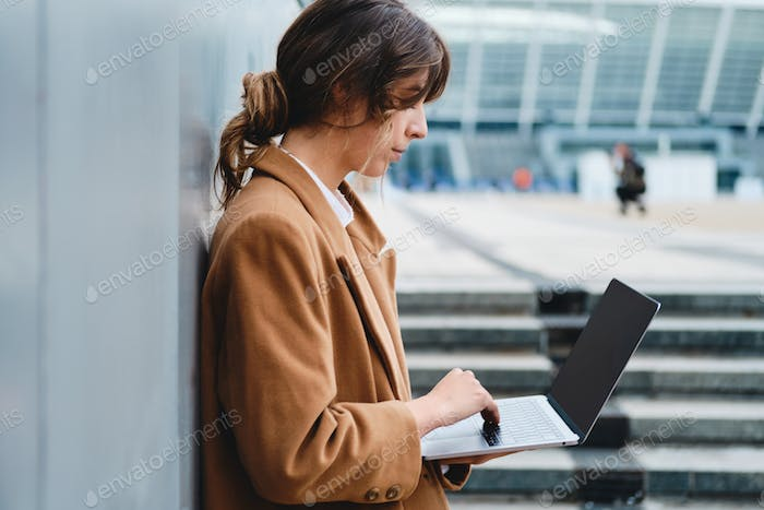 Side view of young businesswoman in coat confidently working on laptop on street