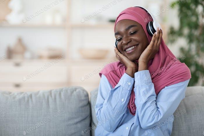 Musik-Liebhaber. Entspannte schwarze muslimische Frau genießt Lieblingsmelodien in kabellosen Kopfhörern