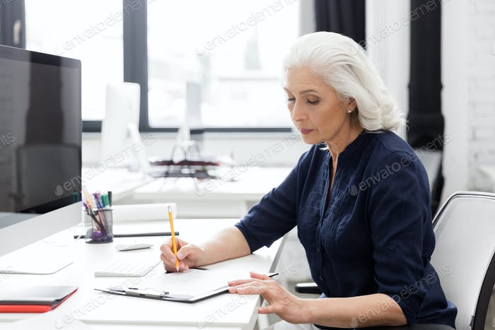 Mature business woman making notes on a piece of paper