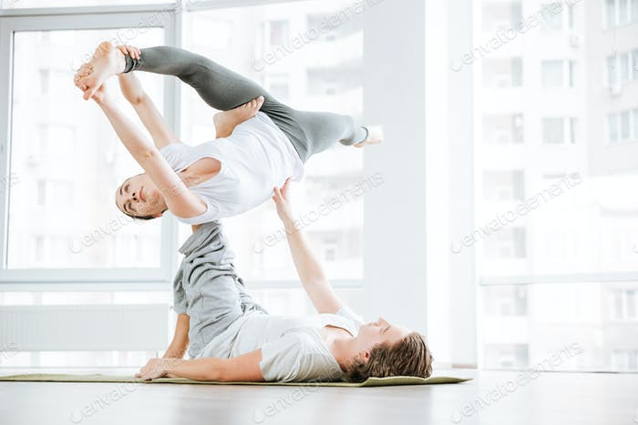 Woman stretching and doing acro yoga with partner in studio