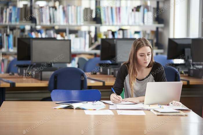 Female Student Working At Laptop In College Library