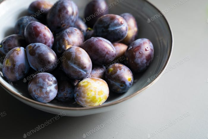 fresh plum fruits in grey bowl on table