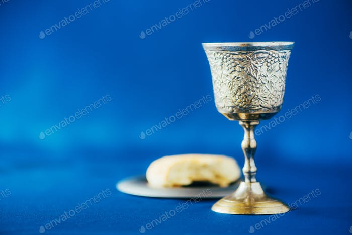 Communion still life. Unleavened bread, chalice of wine, silver kiddush wine cup on blue background