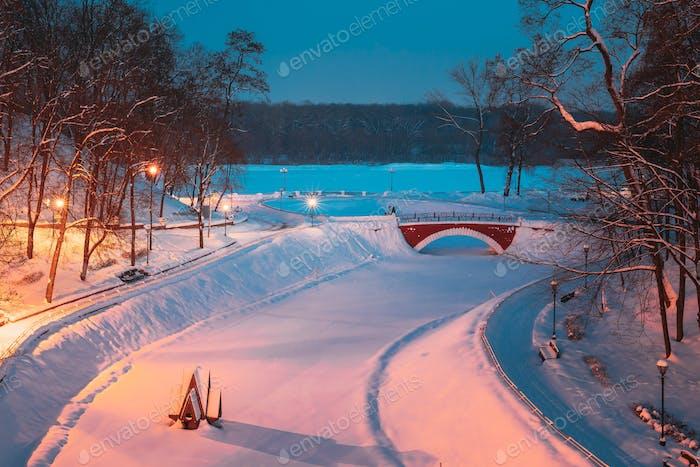 Gomel, Weißrussland. Stadtpark in der Winternacht. Old Bridge And Frozen Teich In Homiel Park, Weißrussland