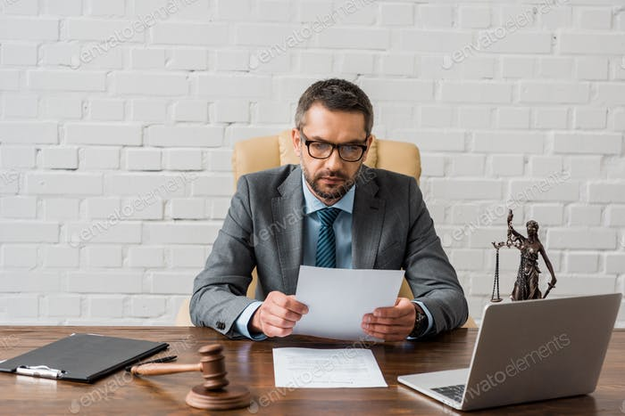 serious male judge working with papers in office