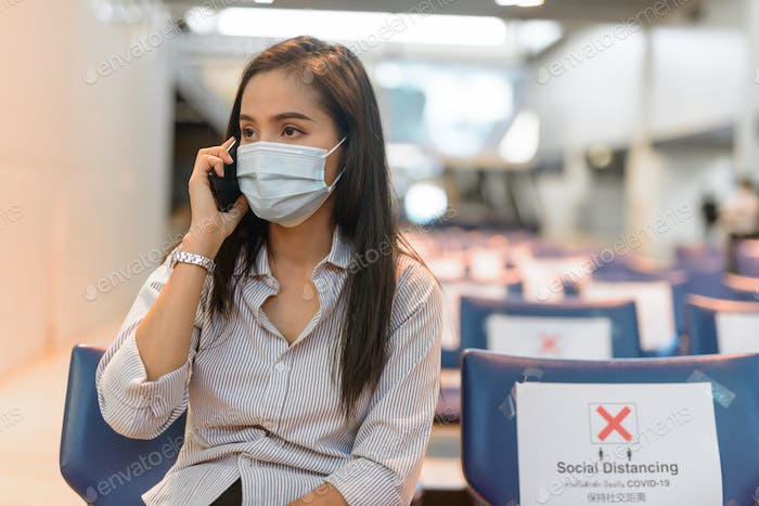 Young Asian tourist woman with mask talking on the phone while sitting with distance at the airport