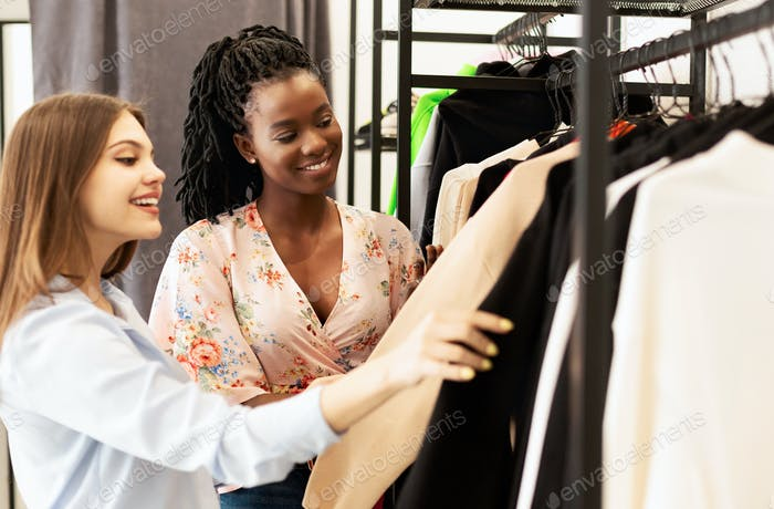 Personal Style Consultant And Client Shopping In Trendy Boutique