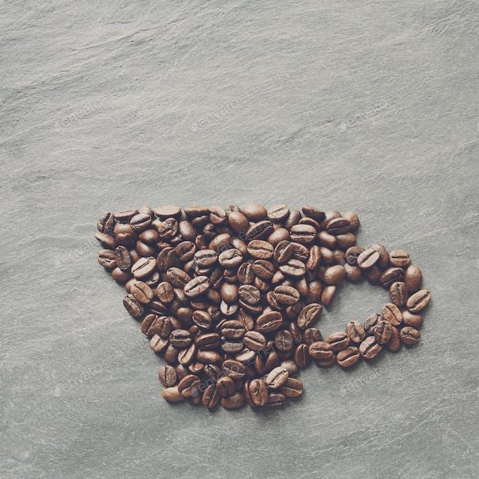 Tasse aus Kaffeebohnen auf Steinhintergrund