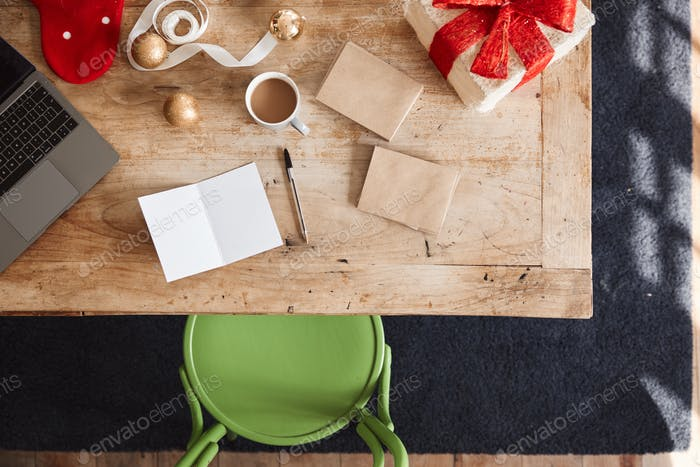 Overhead Shot Looking Down On Blank Christmas Card And Wrapped Gift Wearing On Table