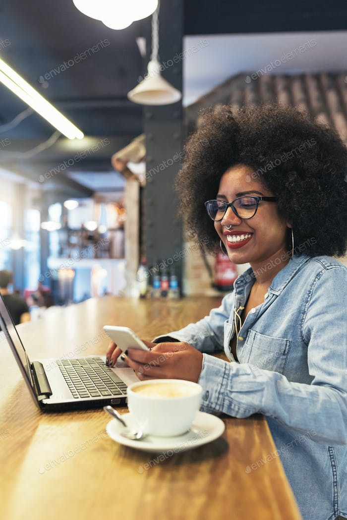 Beautiful afro american woman using mobile and laptop in the coffee shop.