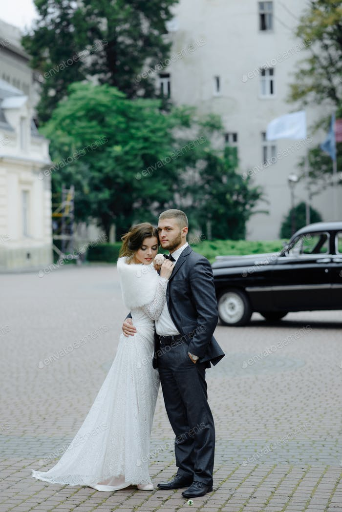 the groom in a gray suit and the bride in a gray dress look at each other, closeup portrait