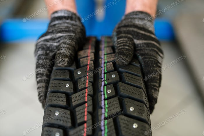 New tyre for car or lorry held by worker of contemporary machine repair service