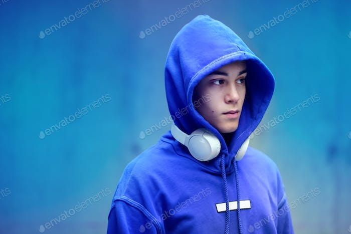 Young man wearing a hoodie with earphones