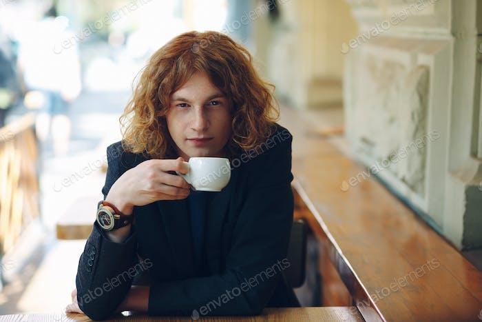 Portrait fashionable reddish man drinking coffee