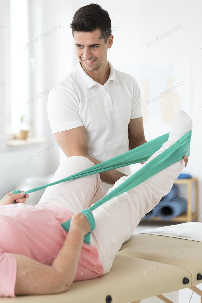 Physician assisting woman in physiotherapy