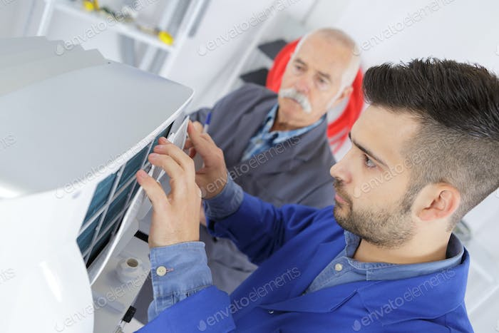 male technician is repairing a printer assited by senior