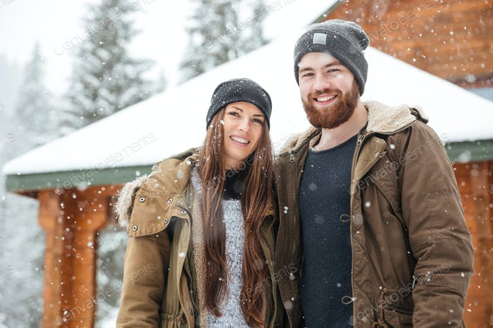 Couple standing in front of log cabine at winter
