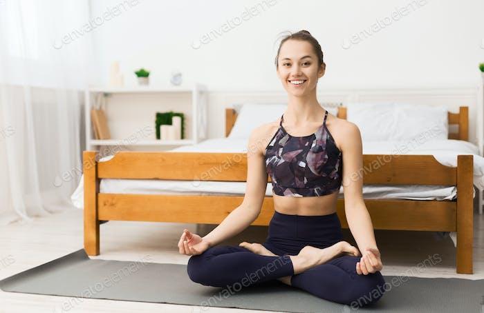 Glückliche Frau tun Yoga-Übung zu Hause
