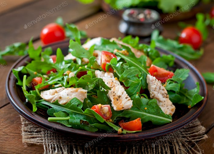 Fresh salad with chicken breast, arugula and tomato.