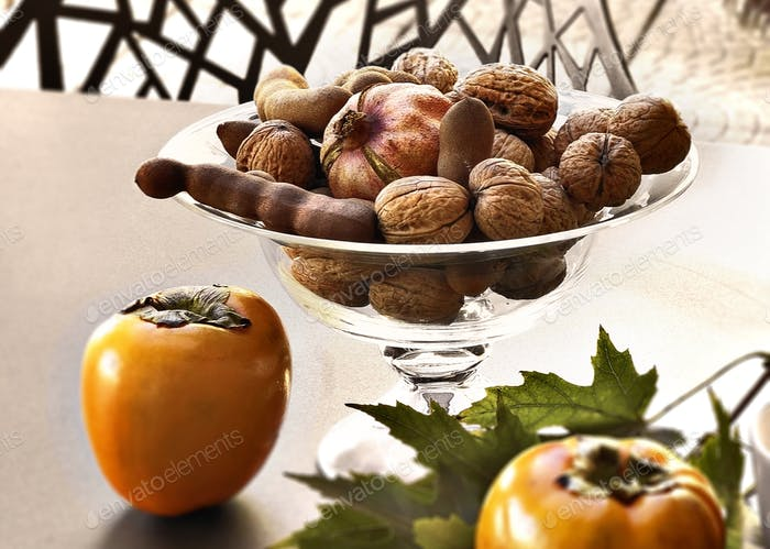 some dried fruit in a glass vase on the terrace table