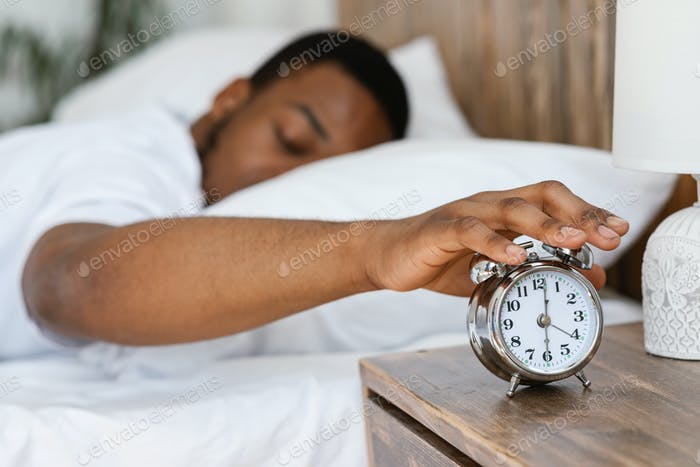 Sleepy Black Man Turning Off Alarm Clock Lying In Bed