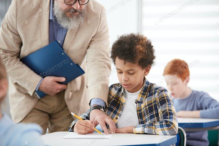 Teacher Helping African American Boy in School