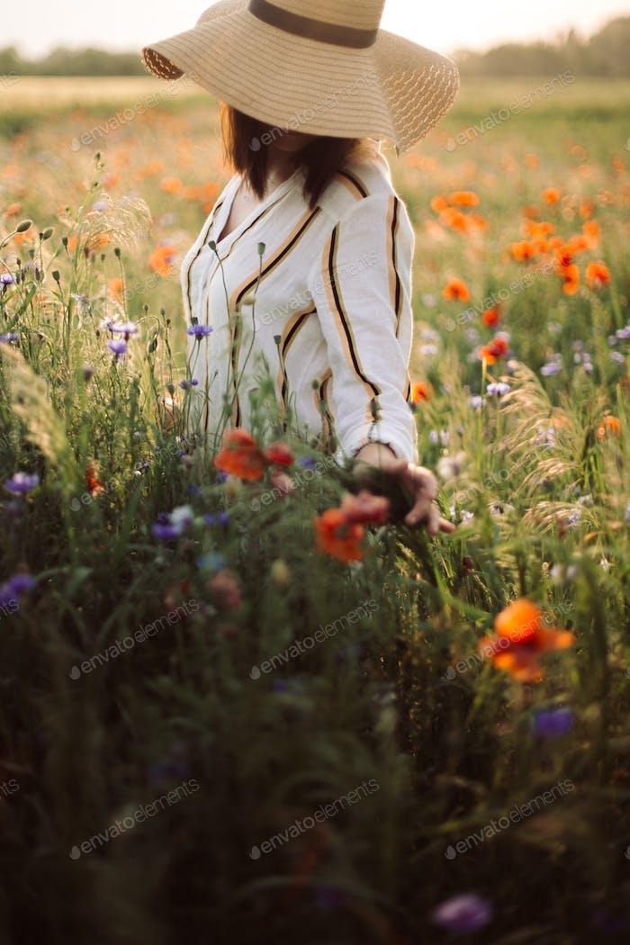 Stylish girl in hat walking in wildflowers in sunset light in summer meadow