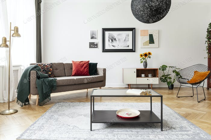 Table on carpet in white apartment interior with sofa, armchair