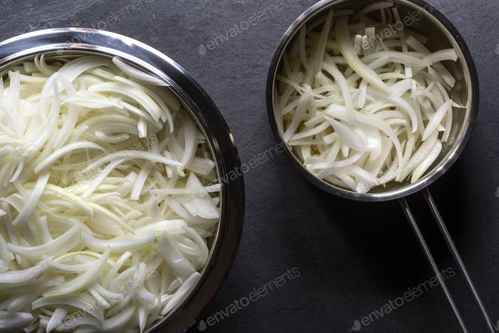 Sliced onions with straws in a bowl and in a saucepan for onion soup