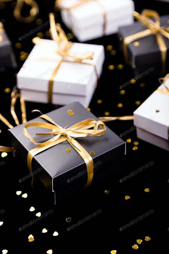 Black and white gift boxes with gold ribbon on shine background. Close up.