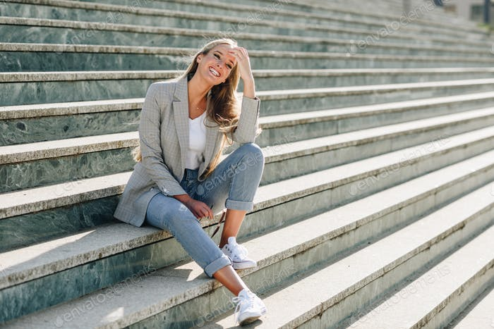 Beautiful young blonde woman smiling on urban steps.