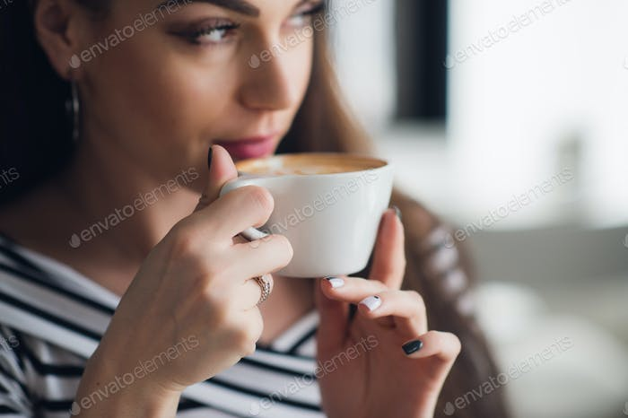 Close up picture of hands holding a cup and woman drinking coffee from it.