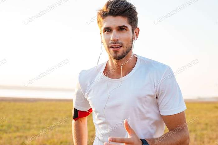 Handsome sportsman running outdoors and listening to music with earphones