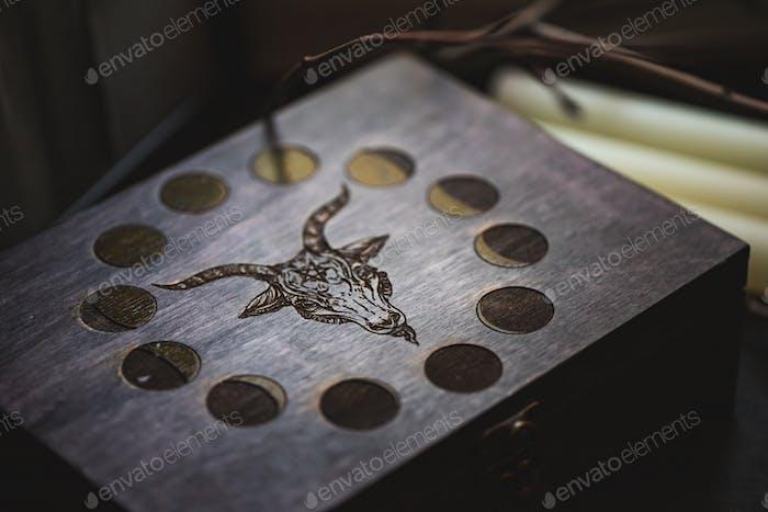 Holzgeschnitzte Box mit dem Bild von Baphomets Kopf und Mondphasen