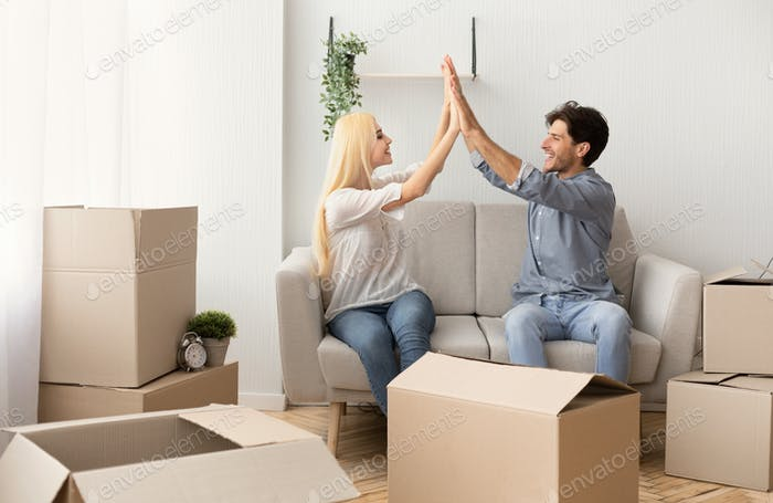 Happy Couple Giving High-Five Sitting On Couch Among Moving Boxes