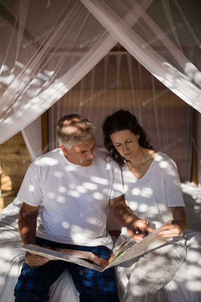 Couple looking at map while relaxing on canopy bed