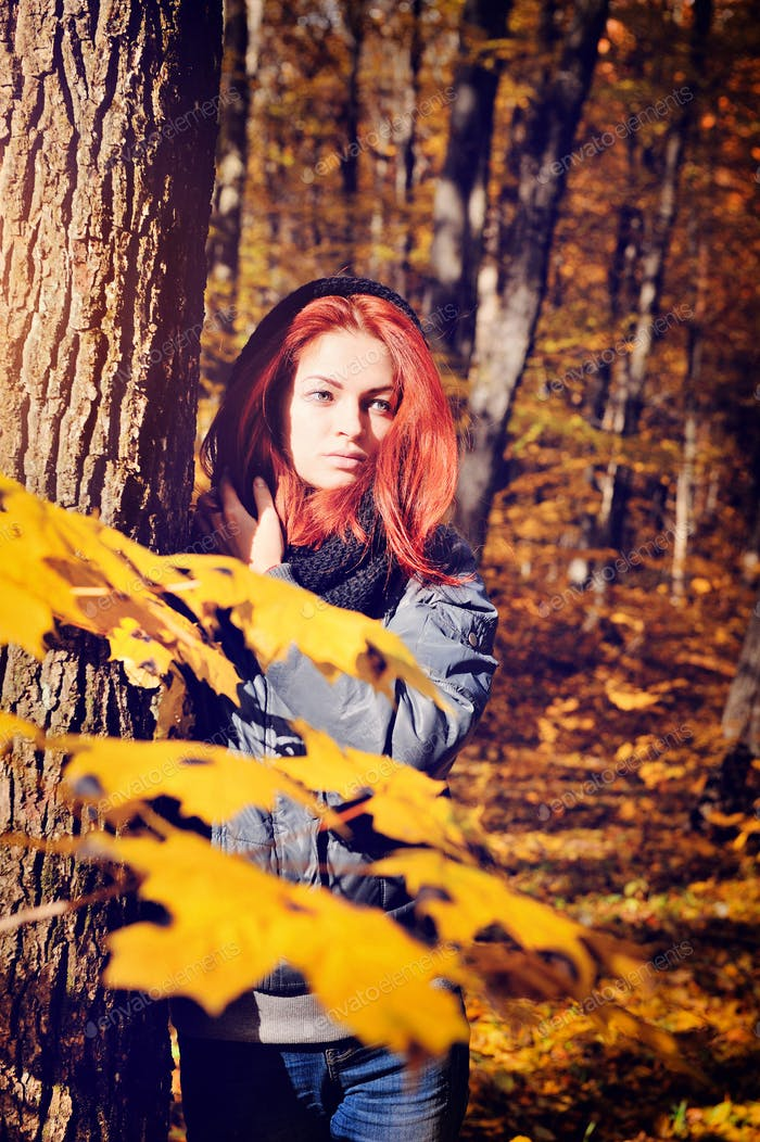 Red-haired girl walking in the autumn forest