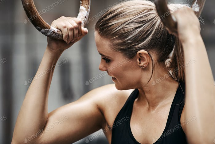 Fit young woman smiling during a workout session with rings