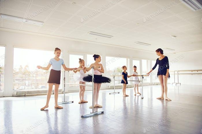 Woman standing with little ballerinas in ballet class