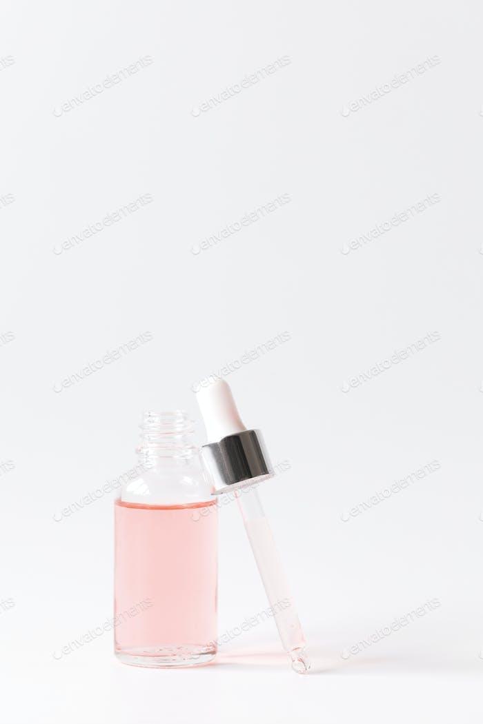 Tropfflasche mit einer Pipette und rosa Wasser.Bio SPA Kosmetik .Mock-Up.