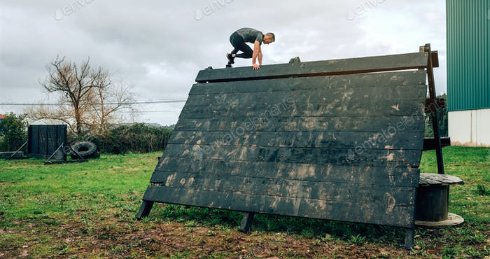 Participant in obstacle course climbing pyramid obstacle