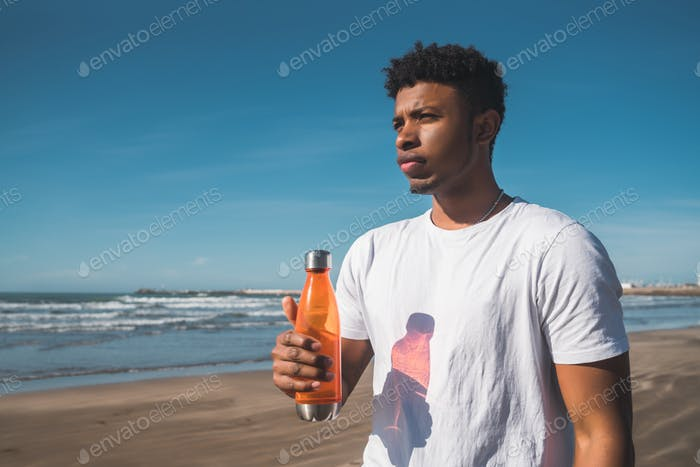 Sportlicher Mann mit einer Flasche Wasser.