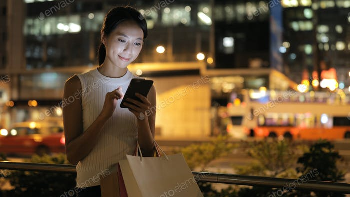 Woman using smart phone and holding shopping bag